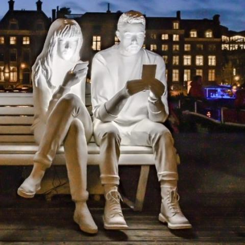 White mannequins illuminated by the screen of their own smartphone, sitting on a street bench